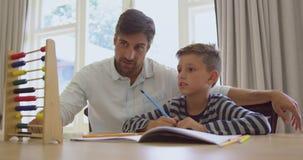 Fader som undervisar hans sonmatematik med kulrammet i ett bekvämt hem 4k stock video