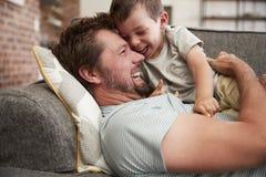 Fader And Son Cuddling på Sofa Together royaltyfri foto