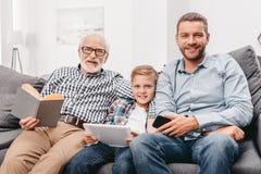 Fader, son och farfar som tillsammans kopplar av på soffan i vardagsrum med den digitala minnestavlan, smartphone arkivfoton