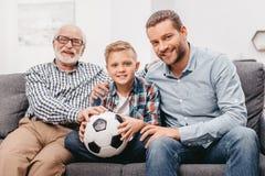 Fader, son och farfar som tillsammans sitter på soffan i vardagsrum royaltyfri fotografi