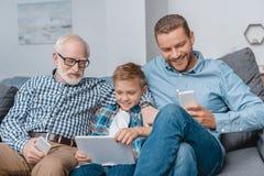 Fader, son och farfar som tillsammans sitter på soffan i vardagsrum med smartphones och den digitala minnestavlan arkivfoton