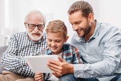 Fader, son och farfar som tillsammans sitter på soffan i vardagsrum och ser digitala arkivfoto