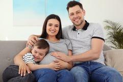 Fader, son och gravid moder som tillsammans spenderar tid på soffan Familj Tid arkivbild
