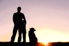 Fader, son och hund framme av solnedgångkonturn Fotografering för Bildbyråer