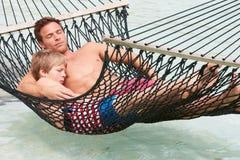Fader And Son Relaxing i strandhängmatta royaltyfria foton