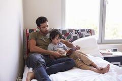 Fader And Son Siting på sängläseboken tillsammans arkivbild