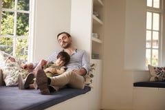 Fader And Son Sleeping på fönstret Seat hemma tillsammans Arkivfoto