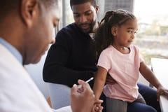 Fader Taking Young Daughter för vaccinering i doktorer kontor royaltyfria bilder