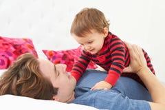 Fader And Toddler Lying i säng tillsammans Fotografering för Bildbyråer