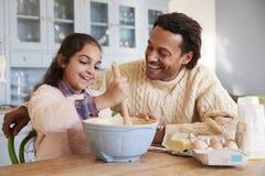 FaderAnd Daughter Baking kakor hemma tillsammans Arkivbilder