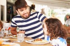 FaderAnd Daughter Enjoying mål i restaurang royaltyfria bilder