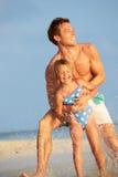 FaderAnd Daughter Having gyckel i havet på strandferie Arkivbilder