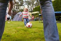 FaderAnd Daughter Playing fotboll i trädgård tillsammans royaltyfri bild