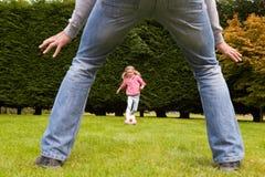 FaderAnd Daughter Playing fotboll i trädgård tillsammans royaltyfria bilder