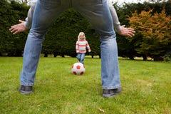 FaderAnd Daughter Playing fotboll i trädgård tillsammans royaltyfri foto