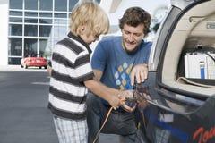 FaderAnd Son Attaching elektrisk propp till bilen Royaltyfri Foto