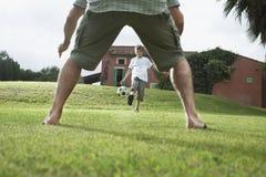 FaderAnd Son Playing fotboll i trädgård Royaltyfri Foto