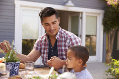 FaderAnd Son Saying Grace Before Outdoor Meal In trädgård royaltyfri fotografi