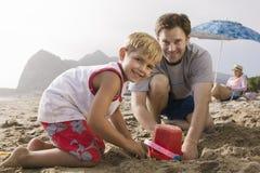 Faderbyggnadssandslott med sonen på stranden royaltyfria foton