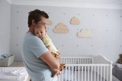FaderComforting Newborn Baby son i barnkammare Fotografering för Bildbyråer
