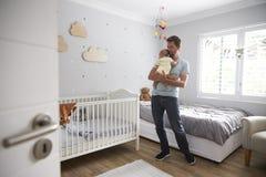 FaderComforting Newborn Baby son i barnkammare Arkivbild