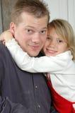 faderflicka som kramar att le royaltyfri foto
