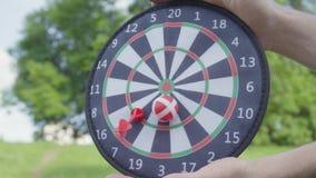 Faderhänderna som rymmer pilar medan hans son som kastar pilar och bollen på en magnet i cirkelnärbilden Familjfritid lager videofilmer