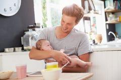 FaderHolding Newborn Baby dotter på köksbordet Royaltyfria Foton