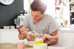 FaderHolding Newborn Baby dotter på köksbordet Fotografering för Bildbyråer