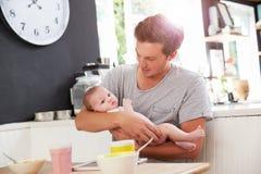 FaderHolding Newborn Baby dotter på köksbordet Arkivbild