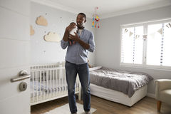 FaderHolding Newborn Baby son i barnkammare Arkivfoto