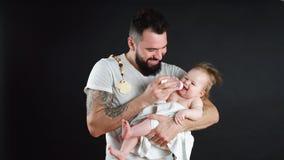 Faderinnehavet och taomsorg av det lilla spädbarnet behandla som ett barn och att mata från flaskan lager videofilmer
