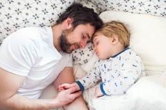 Faderinnehavhand av en sova litet barnpojke i säng hemma royaltyfri fotografi