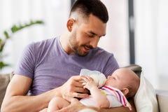 Fadermatning behandla som ett barn dottern från flaskan hemma royaltyfri fotografi
