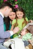 Fadermatningar behandla som ett barn, modern, och dotterblicken på behandla som ett barn i trädgård Fotografering för Bildbyråer