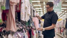 Fadern är att undersöka kläder för ett barn i ett stort lager, hållande hängare arkivfilmer