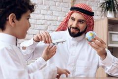 Fadern Arab berättar sonen om flyg av flygplan fotografering för bildbyråer