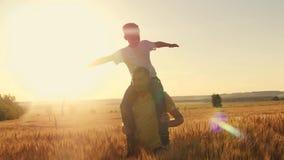 Fadern bär hans son på hans skuldror som A går på vetefältet under solnedgång Familjlek Arkivfoto