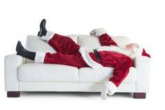 Fadern Christmas sover på en soffa Fotografering för Bildbyråer