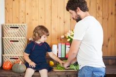 Fadern förbereder vitaminsallad hans gulliga lilla dotter fotografering för bildbyråer