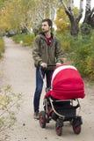 Fadern går med hans barn i barnvagn i parkera Royaltyfria Bilder