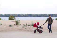 Fadern går med hans barn i barnvagn i parkera förbi Royaltyfri Bild