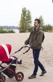 Fadern går med hans barn i barnvagn i parkera förbi Arkivfoton