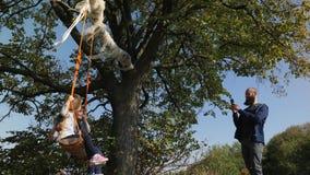 Fadern gör fotoet av hans två döttrar som svänger på en gunga under ett träd lager videofilmer