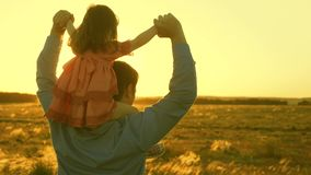 Fadern g?r med hans dotter p? hans skuldror i str?lar av solnedg?ngen Farsan b?r p? skuldror av hans ?lskade barn arkivfilmer