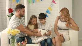 Fadern ger barn en kanin för påsk stock video