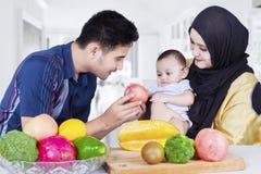 Fadern ger ett äpple till hans behandla som ett barn Royaltyfri Bild