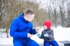 Fadern ger godisen till hans dotter Fotografering för Bildbyråer