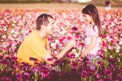 Fadern ger hans dotter en blomma Royaltyfri Bild