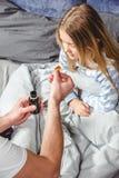 Fadern ger medicin till hans sjukt arkivbild